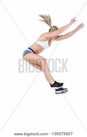 Female athlete jumping on white background