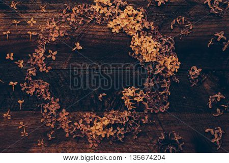 Lilac blossoming flowers decorative wreath on timber background