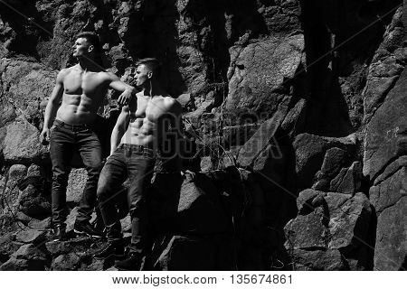 Two men athletic male twins with bare torso in jeans show muscular body abs on rocks black and white on mountain background