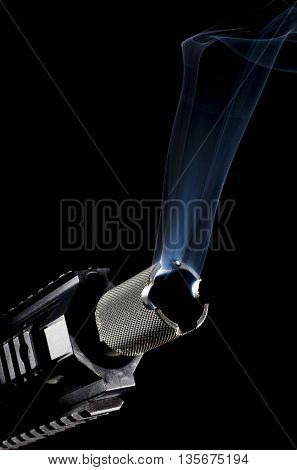 Smoking rising from the barrel of a gun on a black background