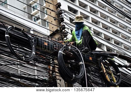 BANGKOK THAILAND - JUNE 18 2016: Unidentified worker works on the power line on the street Bangkok Thailand.