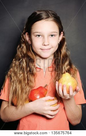 Cheerful little Girl holding two tasty pears.