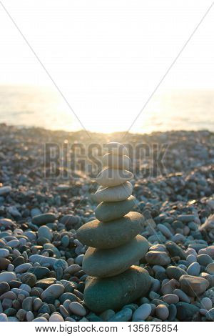 Tower from stones, with lit sun lucha, against the sea.