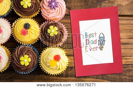 Word best dad ever against delicious cupcakes on a table