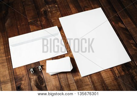 Blank letterhead business cards and envelope. Photo of blank stationery set on vintage wooden table background. Mockup for design portfolios. Blank template for branding identity.