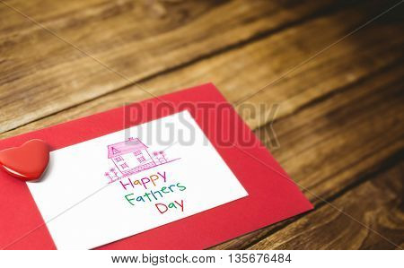 Word happy fathers day and drawn pink house against textured brown wooden floor