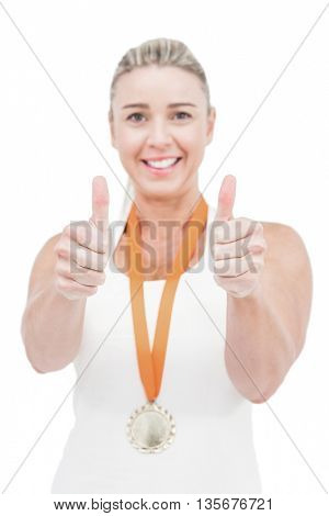 Female athlete wearing a medal and showing thumbs up on white background