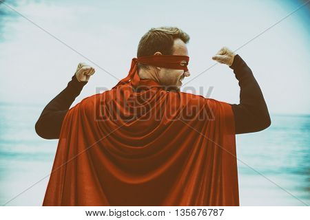 Rear view of man in superhero costume standing at sea shore