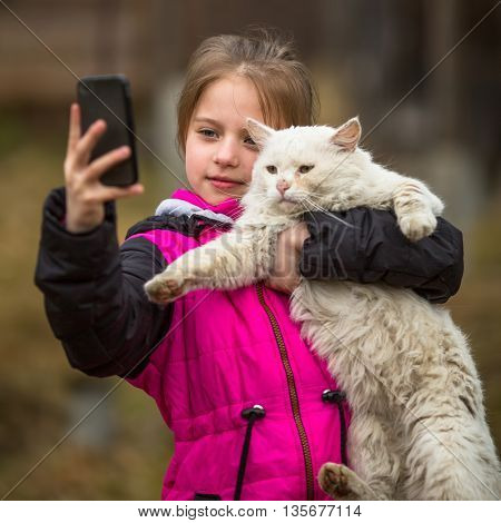 Little girl photographs herself with a stray cat on the phone. Selfie.