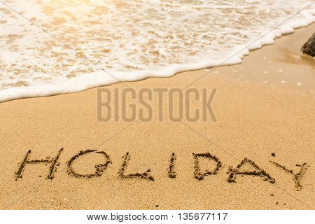 Holiday - word drawn on the sand beach with the soft wave.