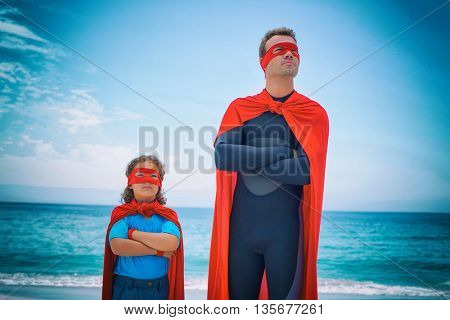 Confident man and son with arms crossed standing at sea shore against sky
