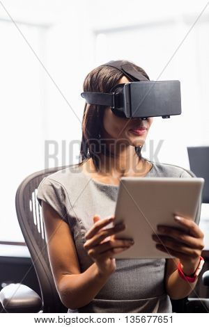 Businesswoman looking her tablet while using a virtual glasses in office