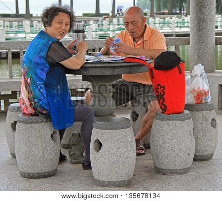 Man And Woman Are Playing Cards Outdoor In Wuhan, China