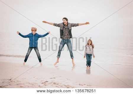 Full length of father enjoying with children at sea shore against sky