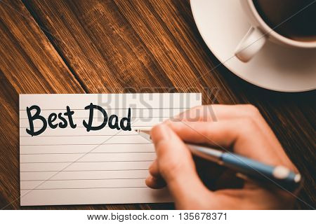 happy fathers day against human hand writing on paper at desk with coffee cup