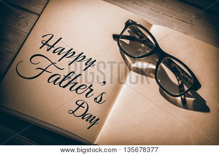 Happy fathers day written on notebook on table