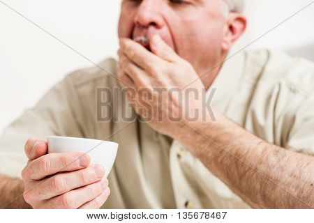 Cropped Head And Shoulders Of Yawning Man With Cup
