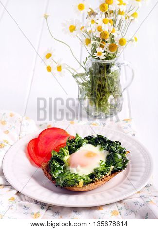 Fried spinach and an egg over toast