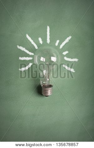 Transparent electric bulb on the green chalkboard (with rays painted with chalk)
