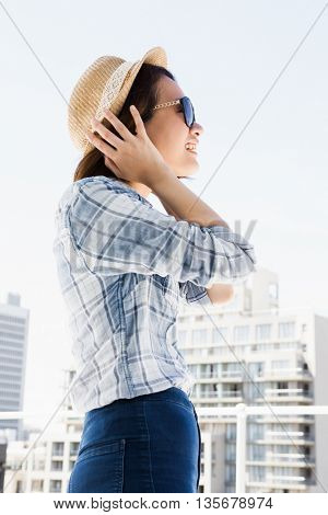 Young woman wearing sunglasses and a hat outdoors