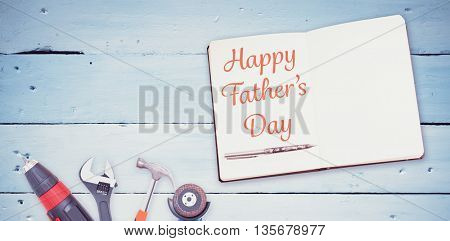 Happy fathers day message written on notebook next to tools