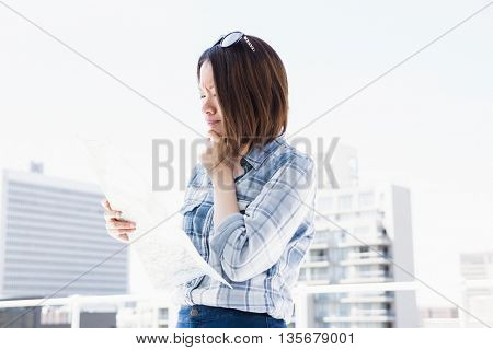 Young woman looking at map for direction outdoors