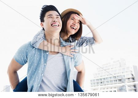 Young man giving a piggyback ride to woman outdoors