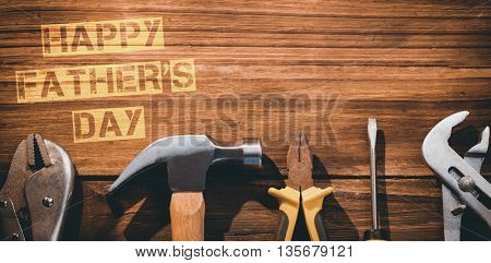 Happy fathers day message next to tools on wooden background