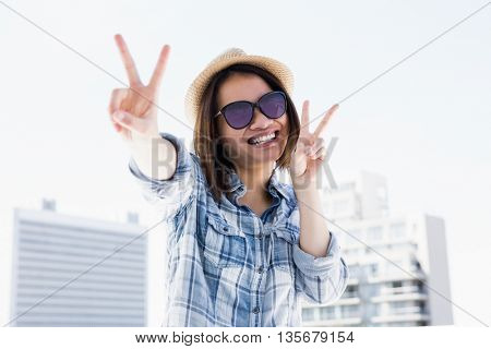 Happy young woman doing a v sign outdoors