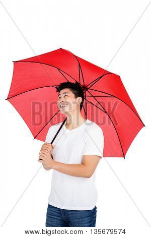 Happy young man holding umbrella on white background