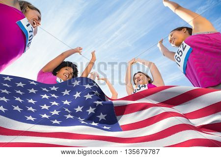 Digitally generated american flag rippling against five cheering runners supporting breast cancer marathon