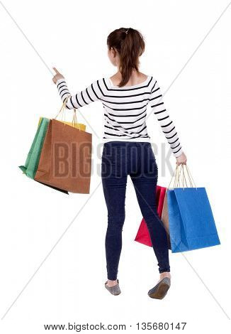 back view of woman  with shopping bags pointing   Rear view people collection. Isolated over white background. Girl in white striped sweater holding purchases in hand and presses the elevator button.