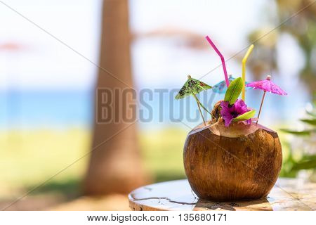 Coconut with drinking straw umbrellas and flowers near a palm tree at the sea