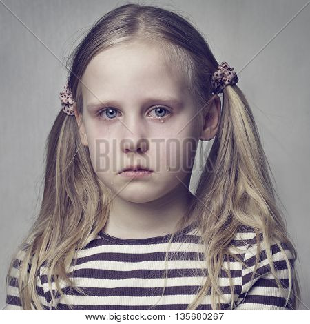 Little girl crying with tears on gray background