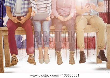 Low section of business people sitting on desk against composite image of usa national flag
