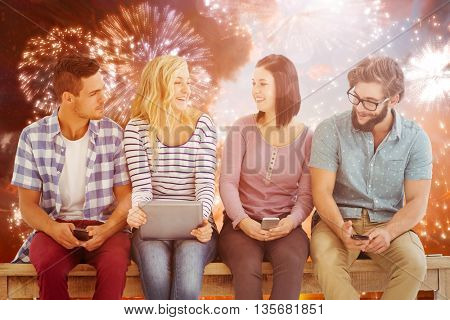 Smiling business people holding electronic gadgets while sitting on desk against colourful fireworks exploding on black background