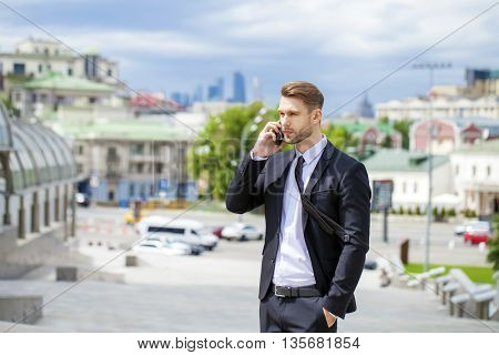 Young successful businessman talking on his cell phone on the street, summer outdoors