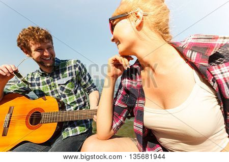 Happy young man hipster playing guitar for woman by sea ocean. Handsome guy and pretty girl in sunglasses relaxing on summer vacation.