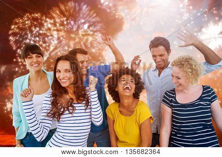 Creative business team having fun against colourful fireworks exploding on black background