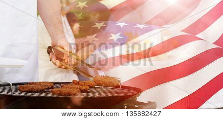 Barbecue grill with extended family having lunch in park against waving flag of america