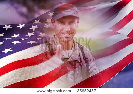 Portrait of happy army man with thumbs up against waving flag of america