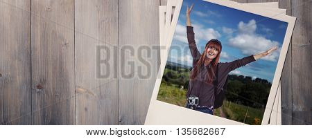 Side view of a hipster woman with a travel bag against pale grey wooden planks