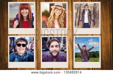 Smiling hipster woman with a travel bag taking selfie against wooden background