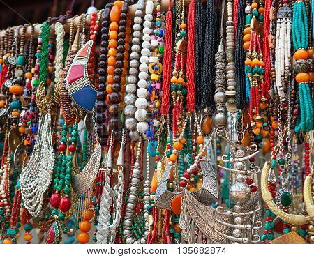 jewelry in row of necklaces and bracelets on summer market outdoors