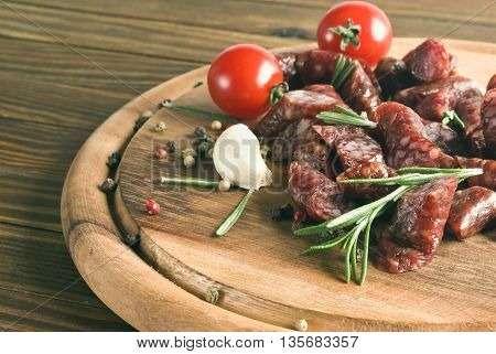 Smoked sausage with rosemary and peppercorns  on a wooden background