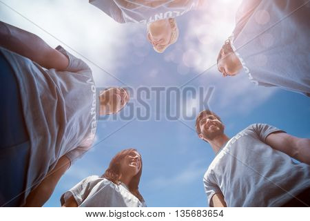 Low angle view of friends together against view of a blue sky