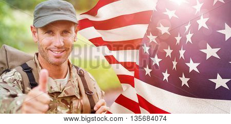 Portrait of happy army man with thumbs up against focus on usa flag