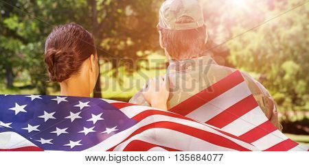 Rear view of solider and wife against focus on usa flag