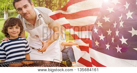 Father and son at barbecue grill with family having lunch in park against focus on usa flag