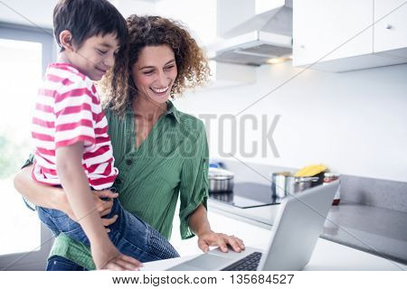 Mother and son using laptop in kitchen at home